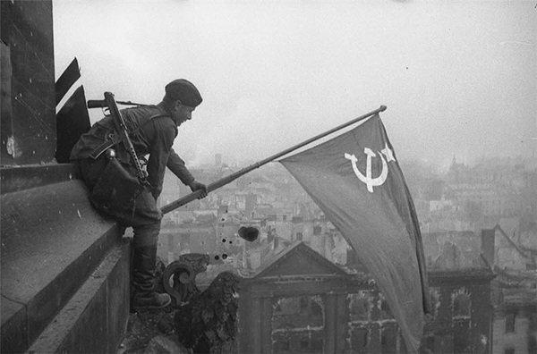 Солдат с ППС-43 водружает советское знамя над поверженным Берлином. Май 1945-го года