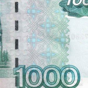 Узор и видимые фрагменты защитной нити на банкноте 1000 рублей модификации 2004 года