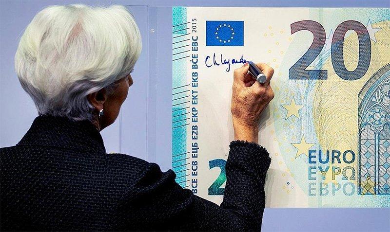 Кристин Лагард символически ставит подпись на банкноте