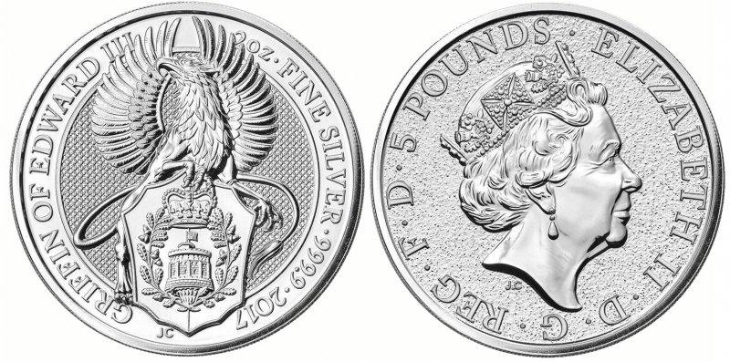 Серебряная монета 5 фунтов. Грифон держит герб Эдуарда III (1327-1377). На щите изображена Круглая башня Виндзорского замка (где родился Эдуард) с королевским штандартом, реющим над ней. Башня окружена двумя ветвями дуба и увенчана королевской короной