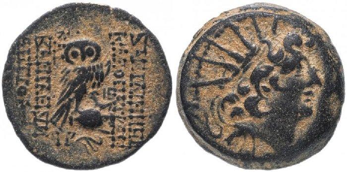 Бронзовая монета с совой, номинал AE19, Селевкиды, Клеопатра Тея и Антиох VIII, 125-121 гг. до н.э. На аверсе сова, сидящая на опрокинутой амфоре. На реверсе Антиоха VIII в солярном венке, повернутая вправо