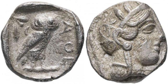 Серебряная тетрадрахма, Аттика, Афины, 454-404 годы до Р.Х. На реверсе изображена сова, голова которой анфас, тело развернуто вправо. В верхней части денежного знака ветвь оливы и полумесяц. Аверс украшает голова Афины в шлеме с растительным узором, в ухе круглая серьга