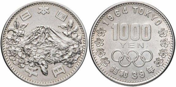 1000 иен 1964 года. На аверсе гора Фудзи. На реверсе номинал монеты, олимпийские кольца и год проведения олимпиады в Токио
